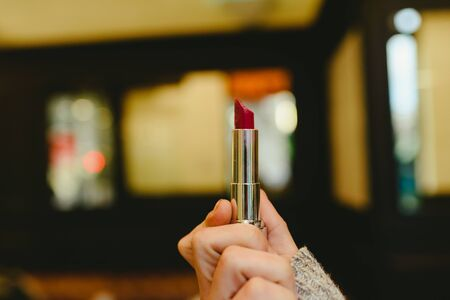 Red lipstick held by a womans hand. Zdjęcie Seryjne