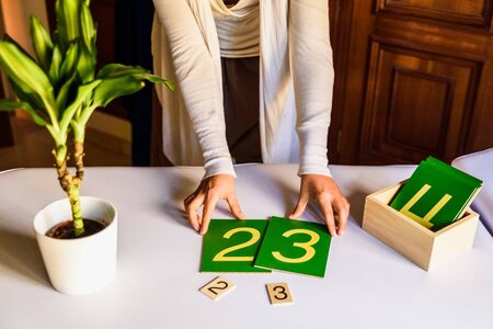 Hands of a montessori teacher guide presenting how to make sums.