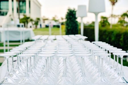 Background of transparent glasses and cups, empty and clean, prepared by a catering for drinks and celebrate an event with diners. Imagens