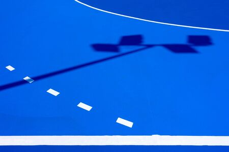 Intense blue background, from the floor of a basketball court to the midday sun, with straight lines and white curves. Reklamní fotografie