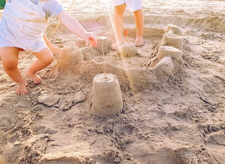 A boy and a baby, siblings, playing sandcastle building on the beach on a summer afternoon near their holiday hotel. Imagens