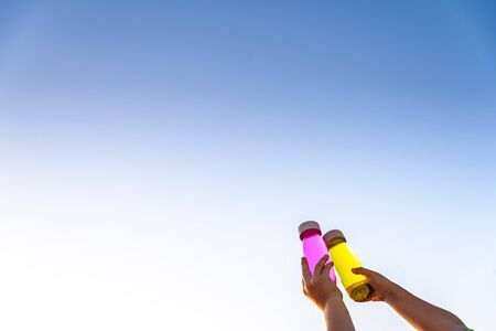 Happy kids toasting with toy bottles of vibrant colors with blue sky background. Zdjęcie Seryjne