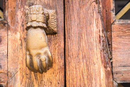 Old hand-shaped knob to knock on an old wooden door.