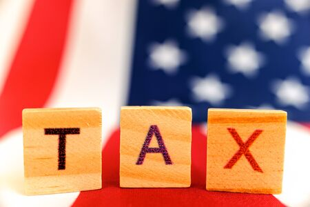 Word Tax on unfocused background of an American flag.