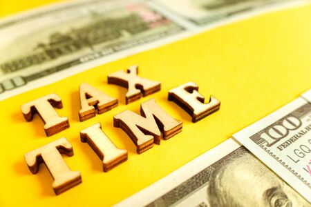 Word Tax Time on yellow background framed with dollar bills.