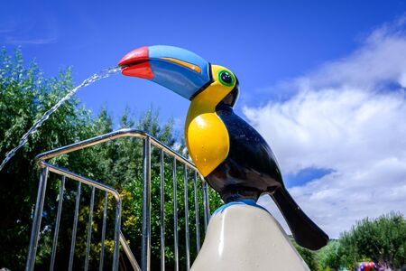 Water fountain shaped like a toucan, tropical bird, in a water park.