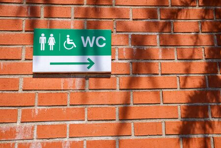 Plaque indicating the direction of disabled toilets on a brick wall.