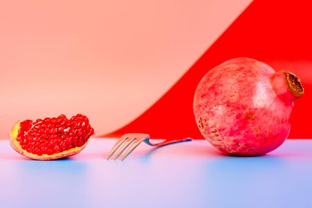 Autumn is the time of pomegranates, open fruit isolated on plain colored backgrounds.