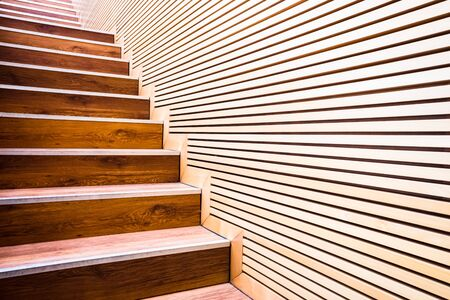 Steps on a ladder next to a wall of wooden boards in sustainable construction. Stockfoto
