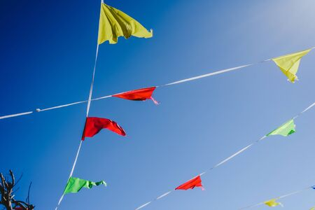 Colored flags against the sun waving in the wind at an outdoor party. Reklamní fotografie