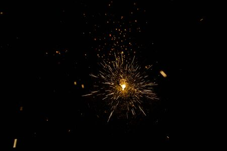 Sparks of a fire during the night, black background.