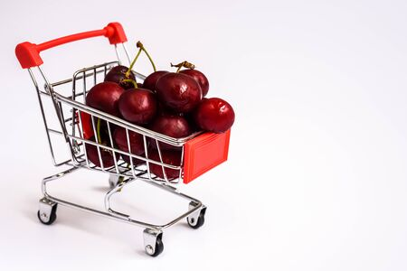 Shopping cart full of ripe cherries, healthy and nutritious shopping full of vitamins to feed children with fruits.