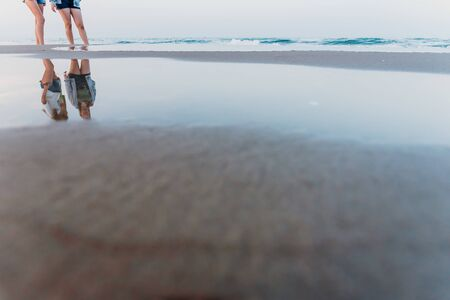 Two friends walking at sunset on a beach, reflecting in the puddles of sand.