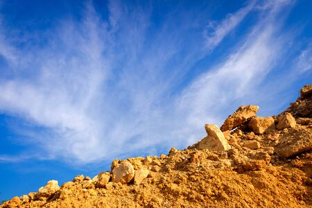 Blue sky background with clouds with some orange rocks. Reklamní fotografie