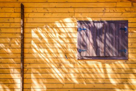 Wall of a wooden plank house with closed window with sun and shadows.