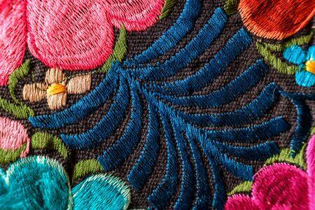 Hintergrund von handgestickten Blumen auf einem Stoff mit farbigen Fäden. Standard-Bild