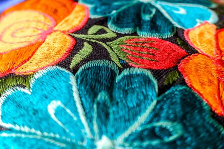 Detail of a colorful embroidery with flower motifs in brightly colored fabrics. 스톡 콘텐츠