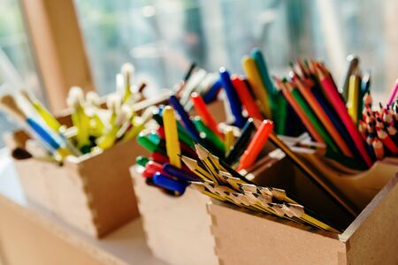 Boxes full of pencils and markers inside a classroom at a childrens school.