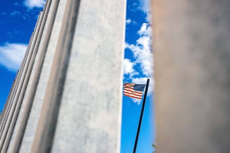 American flag waving across the border seen behind the bars of a barrier against immigrants.