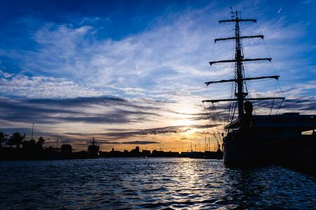 A classic sailboat moored to port in a beautiful sunset.