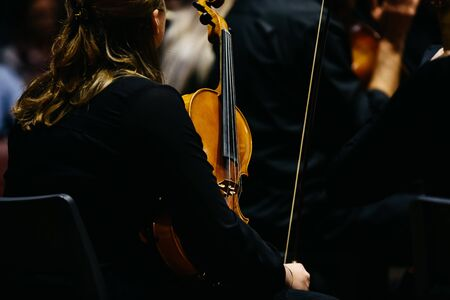Woman fiddler during a concert, background in black. Banque d'images