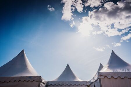 Peaks of three pyramidal white tents and blue sky background with space for advertisers text.