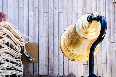 Golden bronze bell on the deck of a sailboat. Stok Fotoğraf