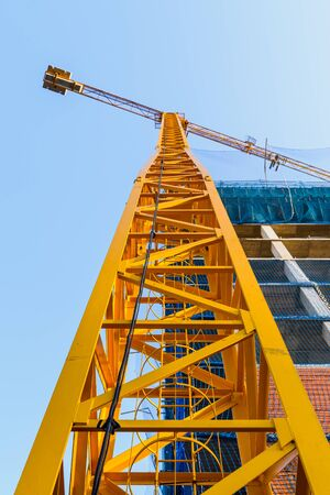 Yellow crane in a construction site to lift large weights of construction material and for the masons to complete their work.