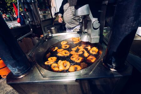 Valencia, Spain - March 19, 2019: Pot with boiling oil to prepare traditional pumpkin fritters buñuelos, in a street stall in Valencia. Редакционное