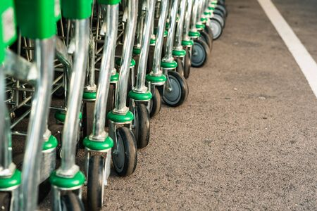 Valencia, Spain - July 3, 2019: Detail of many green metal and plastic supermarket trolleys stacked at the entrance of a store.