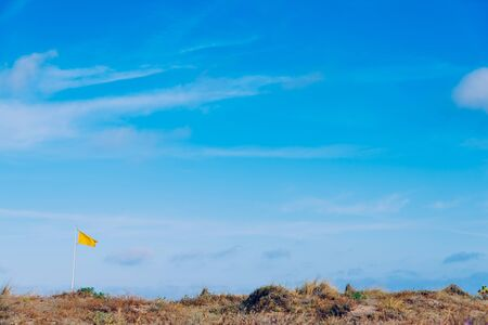 Yellow fabric flag waving to the wind with the background of a clear sky with white clouds.