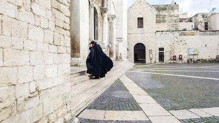 Bari, Italy - March 12, 2019: A Catholic priest walks towards the cathedral dressed in a black cape and hat a day of wind and rain.