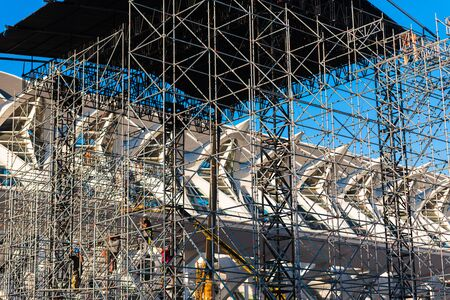 Valencia, Spain - May 28, 2019: Construction of a stage for outdoor musical concerts by workers specialized in work at height equipped with helmets and harnesses. Редакционное