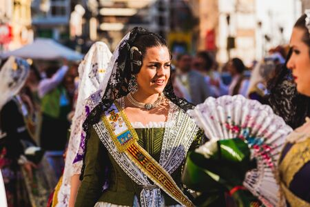 Valencia, Spain - March 17, 2019: The Valencian women wear the traditional fallero suit and the typical hairstyle with bow adorn with luxurious earrings and jewelry necklaces during the Fallas.