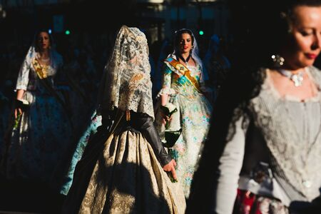 Valencia, Spain - March 17, 2019: Group of Falleras parading through the streets of Valencia to show their colorful and traditional dresses.