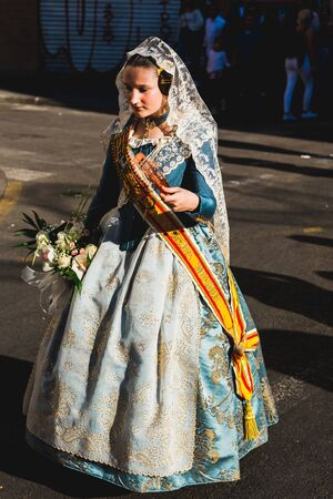 Valencia, Spain - March 17, 2019: Girls Falleras excited with their beautiful traditional costumes arriving at the Cathedral of Valencia to deliver their bouquet of flowers to the Virgin. Редакционное