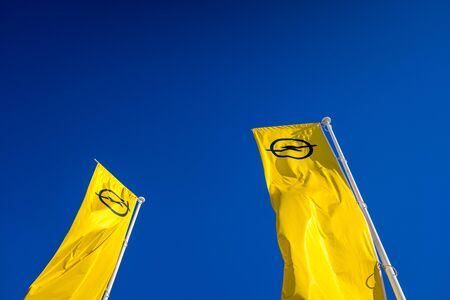 Valencia, Spain - December 3, 2019: Yellow flags with the logo of Opel Automobile GmbH, car manufacturing company.