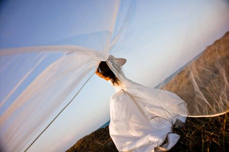 Newly-married bride with wedding dress on top of a hill letting her veil flutter in the wind, romantic image. 版權商用圖片