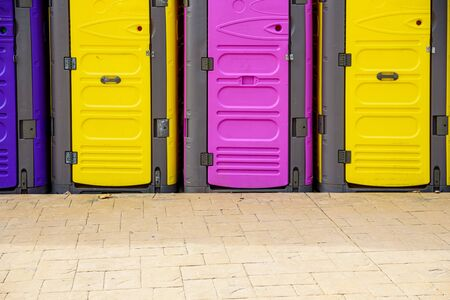 Portable plastic toilets in bright colors, placed on the street during an event. Stock fotó