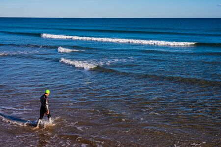 Young athlete enters the sea to swim, wearing a hat and wetsuit.