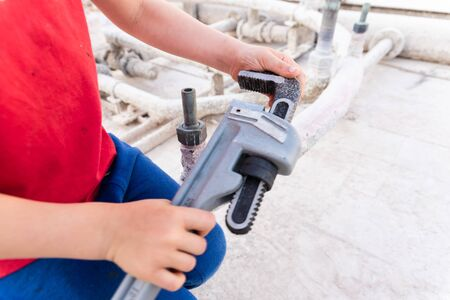 Children using a heavy-duty straight pipe plumbing wrench to repair a pipe.
