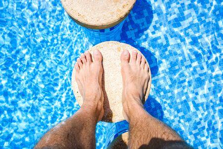Pieds d'un vacancier relaxant dans une piscine. Banque d'images