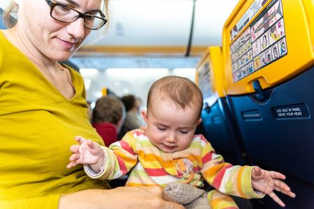 Valencia, Spain - March 19, 2019: Baby entertaining in the arms of his mother sitting in the seat of an airplane during a long trip. Редакционное