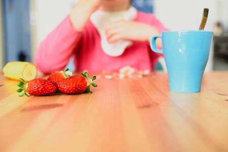 Detail of breakfast with strawberries on a child's table.