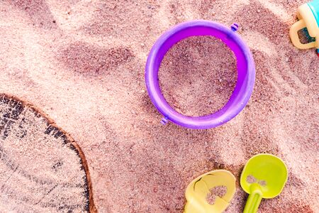 Plastic toy buckets and shovels in a sandpit viewed from above with copy space
