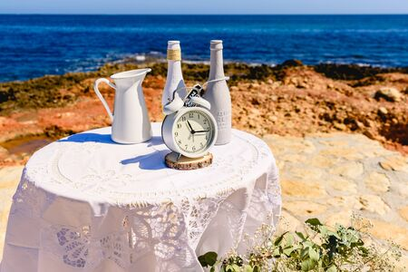 Antique alarm clock next to white decoration bottles, on a round table overlooking the sea and rocks, blue sky background and copy space. Stock Photo