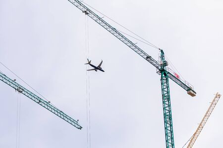 Valencia, Spain - December 20, 2019: Ryanair plane flies over the city framed among building construction cranes, cities grow with tourism.