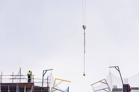 Construction worker on top of a building under construction directing a crane. Zdjęcie Seryjne