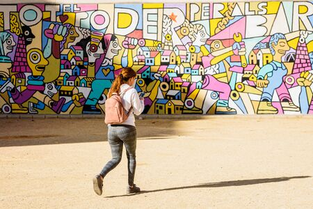 Valencia, Spain - December 21, 2019: Young girl walks in front of an artistic mural while listening to music through her headphones.