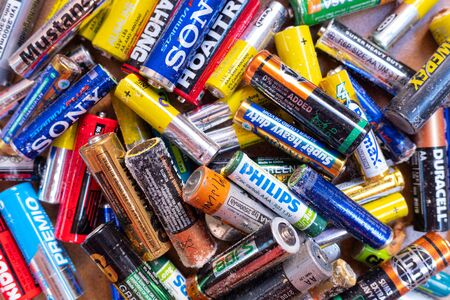 Valencia, Spain- July 24, 2019: Pile of old and used AA and AAA batteries, damaged and broken by acid, ready to send a clean recycling point. Редакционное